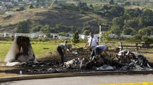 RCMP and the coroner look through the burnt wreckage of a twin engine plane crash at Marshall Field in Vernon, B.C., Saturday, July 7, 2012. (Jeff Bassett/THE CANADIAN PRESS)