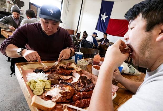 Jonathan Yen (left) and friend Alex Li tackle the Adamson Barbecue specialty plate.