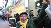 A customer, Song Tae-min reacts after buying a new iPad Mini in Seoul, South Korea, Friday, Nov. 2, 2012. (Ahn Young-joon/AP)