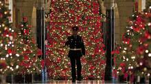 A House of Commons security guard walks through the decorated halls Parliament on Dec. 9, 2011. (Adrian Wyld/Adrian Wyld/The Canadian Press)