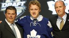 Morgan Rielly, centre, a defenseman, stands with officials from the Toronto Maple Leafs after being chosen fifth overall in the first round of the NHL hockey draft on Friday, June 22, 2012, in Pittsburgh. (Associated Press)