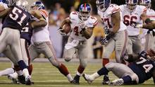New York Giants running back Ahmad Bradshaw (44) runs through a hole in the line during the first half of the NFL Super Bowl XLVI football game against the New England Patriots, Sunday, Feb. 5, 2012, in Indianapolis. (Associated Press)