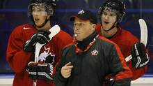 Canada's Ryan Nugent-Hopkins and Jonathan Huberdeau stand behind head coach Steve Spott during team practice (MARK BLINCH/REUTERS)