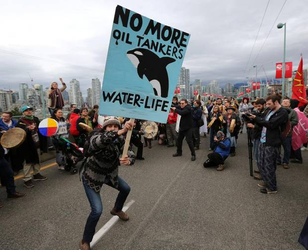 A protester dances with a sign during a march against the proposed expansion of Kinder Morgan's Trans Mountain Pipeline, on the Cambie Street bridge in Vancouver, B.C., on November 19, 2016.