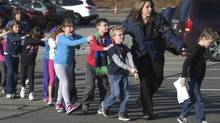 In this photo provided by the Newtown Bee, Connecticut State Police lead a line of children from the Sandy Hook Elementary School in Newtown, Conn. after a shooting at the school. (Shannon Hicks/AP Photo/Newtown Bee)
