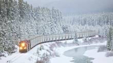 A Canadian Pacific train travels along a highway near Lake Louise, Alta., under fresh fallen snow in November 2011. (Chris Bolin for The Globe and Mail)