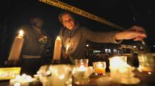 Glenn and Susan Robitaille light candles at a vigil set up outside the Algo Centre in Elliott Lake on June 25, 2012. (Fred Lum/The Globe and Mail)