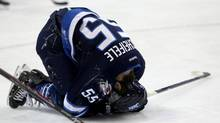Winnipeg Jets' Mark Scheifele (55) is hurt on the ice against the New York Islanders during second period NHL hockey action in Winnipeg, Tuesday, March 4, 2014. (Trevor Hagan/THE CANADIAN PRESS)