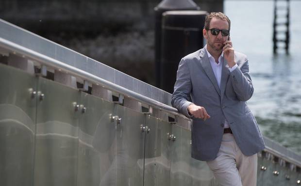Liberal Leader Justin Trudeau's chief advisor Gerald Butts speaks on his phone as Trudeau holds a news conference in North Vancouver, B.C., on Friday May 29, 2015.