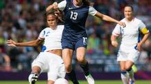 United States' Alex Morgan, center, is challenged by France's Wendie Renard, left, during their women's group G soccer match prior to the start of the London 2012 Summer Olympics, Wednesday, July 25, 2012, at Hampden Park Stadium in Glasgow. (Chris Clark/AP)