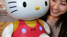 A Japanese woman smiles next to Hello Kitty Robo, developed by Japanese robot maker Business Design Laboratory, at the 2005 International Robot Exhibition in Tokyo. (YURIKO NAKAO/REUTERS)