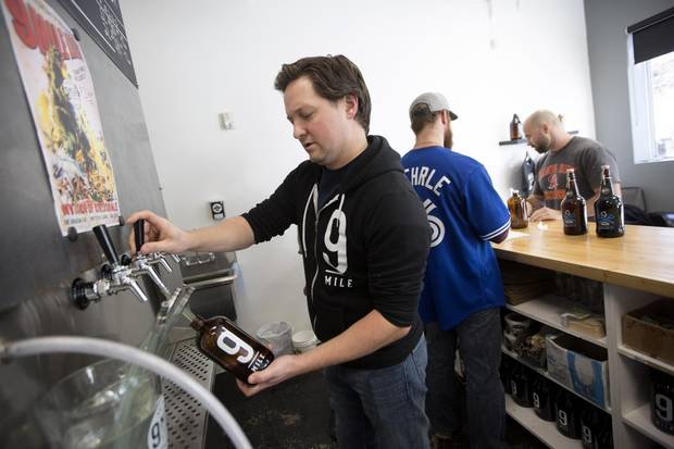 Co-founder of 9 Mile Legacy Brewing Shawn Moen fills a bottle with his craft ale. David Stobbe for the Globe and Mail