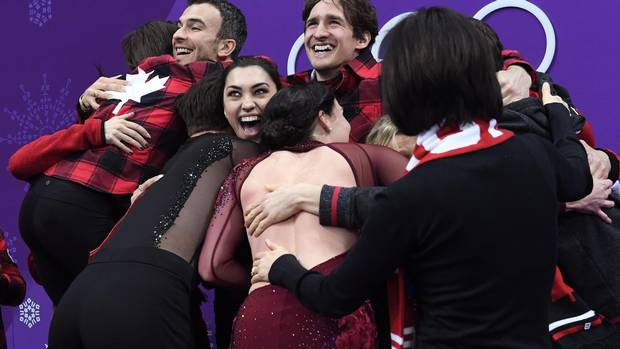 Canada's athletes hug after they won the figure skating team event title during the Pyeongchang 2018 Winter Olympic Games at the Gangneung Ice Arena in Gangneung, on Feb. 12, 2018.