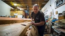 Artist Joe Mandur works on a 40-foot totem pole in honour of the late artist and teacher Freda Diesing, in his garage near Terrace, B.C. on May 8, 2014. Joe Mandur is looking for 3,000 people to join him in carving the pole and so far 500 have accepted. (John Lehmann/The Globe and Mail)