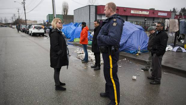 Donna May, left, whose daughter Jac Gray frequented the Surrey Strip shortly before dying of an overdose in August, 2012, stop to talk to an RCMP officer during a visit in the area known as