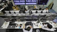 Money traders work at computer terminals with screens indicating the U.S. dollar which is traded at 104.309 yen at a foreign exchange company in Tokyo, Wednesday, Jan. 15, 2014. (Shizuo Kambayashi/AP)