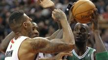 Boston Celtics' forward Kevin Garnett (R) looks to pass against Toronto Raptors' defenders James Johnson (front L) and Ed Davis during the first half of their NBA basketball game in Toronto April 13, 2012. REUTERS/Mike Cassese (Mike Cassese/Reuters)