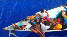 Somali migrants in a disabled skiff wait for assistance from sailors aboard the guided-missile cruiser USS Lake Champlain (DANIEL BARKER AFP)