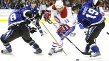 Montreal Canadiens' Scott Gomez (11) controls the puck against the Tampa Bay Lightning's Randy Jones (8) and Dominic Moore (19) during the first period of an NHL hockey game Saturday, March 5, 2011, in Tampa, Fla. The Canadiens won 4-2. (AP Photo/Brian Blanco) (Brian Blanco)