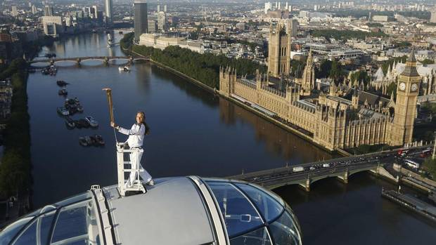 Torch bearer Amelia Hempleman-Adams, age 17, stands on top of a capsule on the London Eye as part of the torch relay ahead of the London 2012 Olympic Games in London July 22, 2012. (LUKE MACGREGOR/Reuters)