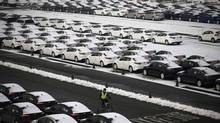 A worker cycles past cars made by South Korea's Hyundai Motor and affiliate Kia Motors awaiting shipping at a port in Pyeongtaek, south of Seoul. (KIM HONG-JI/REUTERS)
