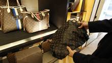 A fake LVMH handbag (R) purchased and shipped from a China -ased online website is pictured next to products on display at a Louis Vuitton store in Chevy Chase, Maryland, October 5, 2010. The Organization for Economic Cooperation and Development estimates the amount of counterfeit goods and pirated copyrights in world trade grew from about $100 billion in 2001 to about $250 billion in 2007, the last year for which they have made an estimate. In the 2009 budget year, U.S. Customs agents and other officials made 14,481 seizures valued at $260.7 million dollars. Picture taken October 5, 2010. To match Special Report CHINA-PIRACY/ REUTERS/Hyungwon Kang (UNITED STATES - Tags: CRIME LAW BUSINESS)