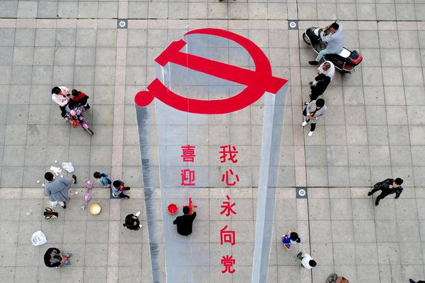 Xiayi, Henan province: A man working on a 3-D street painting of the emblem of Chinese Communist Party.