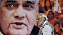 Indian Prime Minister Narendra Modi walks in front of a picture of former Indian Prime Minister Atal Behari Vajpayee after a news conference in New Delhi July 9, 2014. (ANINDITO MUKHERJEE/REUTERS)