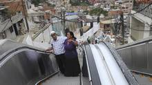 Luis Hernesto Holguin, left, and his sister Resfa Holguin use outdoor escalators, newly installed at Comuna 13 shantytown as part of an urbanization plan to improve living conditions of residents, in Medellin, Colombia. The improvement in Colombia's security situation is critical to its economic prospects. (Luis Benavides/AP)