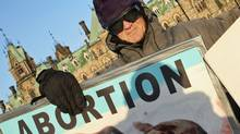An protester waves anti-abortion placards on Parliament Hill in 2006. (Bill Grimshaw/Bill Grimshaw for The Globe and Mail)