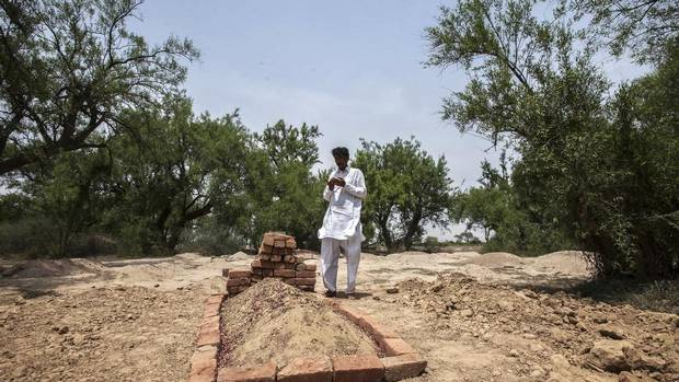 Muhammed Iqbal, 45, prays beside the grave of his late wife Farzana Iqbal in a village in Moza Sial, west of Lahore May 30, 2014. (MOHSIN RAZA/REUTERS)