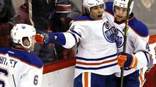 Edmonton Oilers' Nail Yakupov (64), of Russia, celebrates his game-winning goal against the Phoenix Coyotes with teammates Taylor Hall (4) and Ryan Whitney (6)during overtime in an NHL hockey game Wednesday, Jan. 30, 2013, in Glendale, Ariz. The Oilers defeated the Coyotes 2-1 in overtime. Edmonton takes on the Avalanche in Denver on Saturday. (Ross D. Franklin/AP)