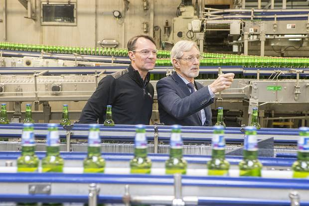 Andrew Oland, president of Moosehead Breweries, left, and father Derek Oland, check on the operations of the packaging line.