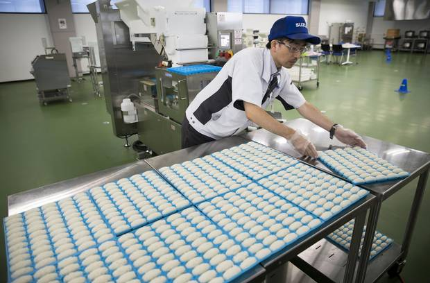 An employee places a tray of sushi rice made by a Suzumo machine on a table at a factory in Saitama, Japan in August. Suzomo's machines are used by about 70,000 customers around the world.