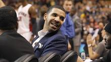 Drake talks with a friend during play between the Toronto Raptors and the Memphis Grizzlies at the Air Canada Centre in Toronto on October 23, 2013. (DEBORAH BAIC/THE GLOBE AND MAIL)