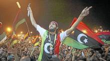 People celebrate the collapse of the Gadhafi regime in Benghazi, Libya, Aug. 22, 2011. (Alexandre Meneghini/AP)