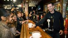 Ontario Premier Dalton McGuinty serves beer after speaking about his party's plan to make post-secondary education more accessible and affordable while at the Regal Beagle pub in Toronto on Sunday September 25, 2011. (THE CANADIAN PRESS / Aaron Vincent Elkaim/THE CANADIAN PRESS / Aaron Vincent Elkaim)
