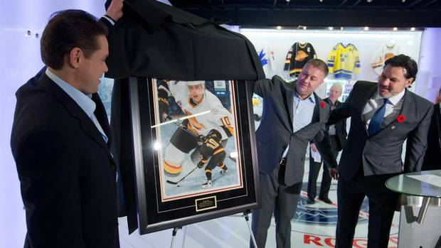 "Retired Vancouver Canucks' forward Pavel Bure, left, of Russia, Canucks' president and general manager Mike Gillis, centre, and team co-owner Francesco Aquilini unveil a painting presented to Bure after the NHL hockey team inducted him into their ""Hall of Heroes"" in Vancouver, B.C., on Friday November 1, 2013. The Canucks will retire Bure's number 10 Saturday before a game against the Toronto Maple Leafs. (DARRYL DYCK/THE CANADIAN PRESS)"