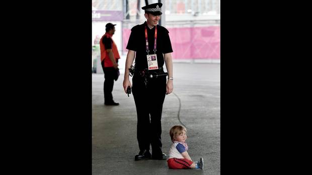 """I'm here for the 2032 Opening ceremonies."" Winning caption by Wendy Hicks on Aug. 10. (A policeman with a child outside a basketball arena at the London Olympics on Aug. 9, 2012.) (Vadim Ghirda/Associated Press)"