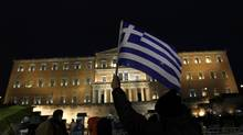 A protester holds up a Greek flag during an anti-austerity demonstration in front of the parliament in Athens Feb. 22, 2012. (YANNIS BEHRAKIS/YANNIS BEHRAKIS/REUTERS)