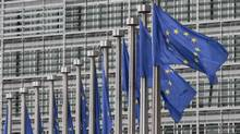 EU flags fly at the European Commission headquarters in Brussels (Yves Logghe/AP)