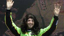James Hinchcliffe waves while wearing a wig during driver introductions for the IndyCar Series' Honda Grand Prix auto race in St. Petersburg, Fla., on Sunday, March 25, 2012. Hinchcliffe replaced Danica Patrick at Andretti Autosport. (AP Photo/LAT, Paul Webb) (Paul Webb/AP)