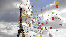 Balloons are released into the air in front of the Eiffel Tower in support of four French journalists being held hostage in Syria. (JACKY NAEGELEN/Reuters)
