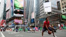 A boy plays basketball as tourists relax in chairs on Broadway in New York's Time's Square, May 26, 2009. Parts of Broadway near Time's Square and Herald Square have been closed to vehicular traffic for use as a pedestrian promenades. (Brendan McDermid/REUTERS)