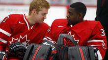 Dougie Hamilton, left, from Toronto, Ont., chats with goalie Malcolm Subban, from Toronto, Ont., during a photo session after the naming of the team at the National Juniors selection camp in Calgary, Alta., Friday, Dec. 14, 2012. (Jeff McIntosh/THE CANADIAN PRESS)