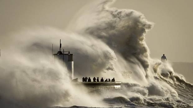 People watch and photograph enormous waves as they break on Porthcawl Harbour, South Wales, Monday Jan. 6, 2014. Residents along the U.K.'s coasts are braced for more flooding as strong winds, rain and high tides lash the country. (Ben Birchall/AP)