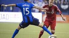 Toronto FC's Kyle Bekker, right, tries to pass Montreal Impact Andres Romero during second half MLS action at the Olympic Stadium in Montreal on Saturday March 16, 2013. (Peter McCabe/The Canadian Press)
