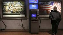 A man stand next to advertisements promoting Canada as a preferable oil provider for America at a metro station in Washington January 29, 2014. (YURI GRIPAS/REUTERS)
