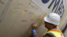 Bruce McCuaig, CEO of Metrolinx, signs one of the tunnel-boring machines in Toronto, Ont. Wednesday, June 5, 2013. The transportation agency says the transit route will cut travel time dramatically. (Kevin Van Paassen/The Globe and Mail)