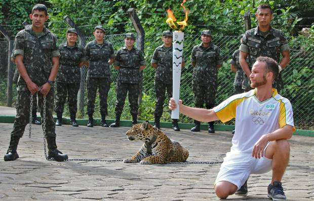 An athlete holds the Olympic torch by a jaguar, a symbol of Amazonia, during a ceremony in Manaus, northern Brazil, on Monday.